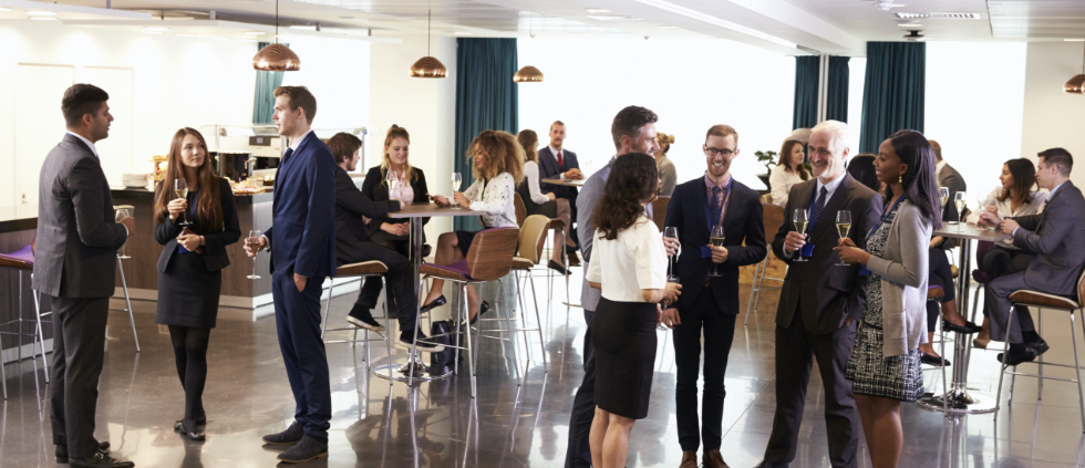 men and women dressed nicely at happy hour networking event talking getting to know each other